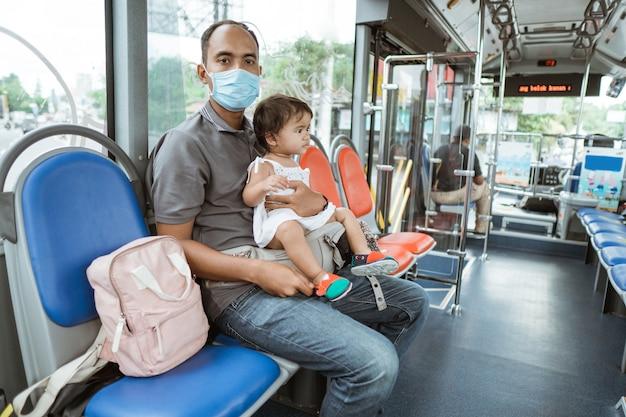 마스크를 쓰고 아버지는 여행하는 동안 버스에 귀여운 아기 소녀를 들고 벤치에 앉아