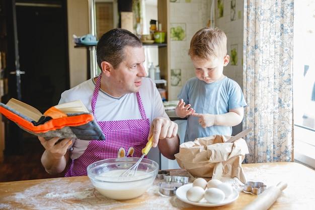 生地を準備する台所のテーブルで若い息子を持つ父