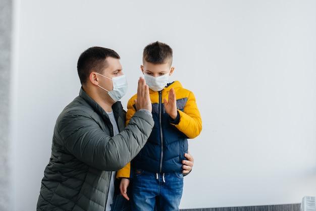 자녀를 둔 아버지는 검역 기간 동안 가면에 서있다. 유행성, 코로나 바이러스.