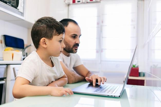 息子と一緒の父親が自宅のキッチンでコンピューターを使用している