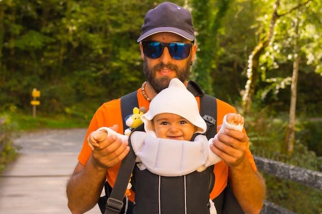 スペインのナバラとフランスの大西洋ピレネー山脈の北にあるイラティの森またはジャングルにあるpasserelledeholzarteに向かうバックパックに赤ちゃんを乗せた父親