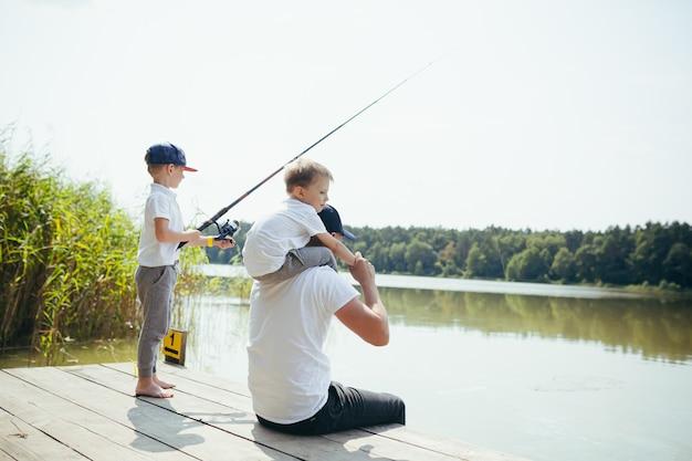 Отец с двумя маленькими сыновьями ловит рыбу на озере летом по выходным.