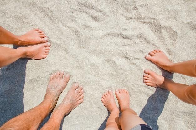 自然旅行の海沿いの幸せな人々の砂の上の足