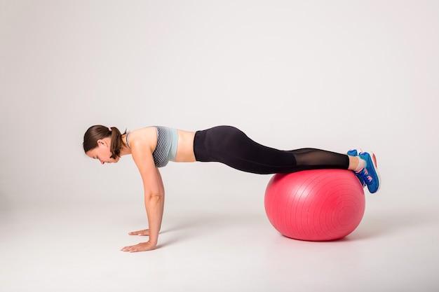女性アスリートはテキスト用のスペースで分離された白のボールにバランス演習を行います