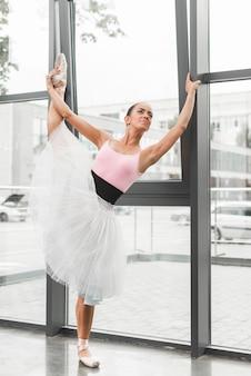 窓の近くに彼女の脚を伸ばしている女性のバレエダンサー