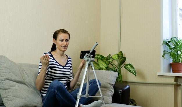 한 여성 블로거가 전화를 들여다보며 화상 통화를 하고 비디오 블로그나 웹 세미나를 녹화합니다.
