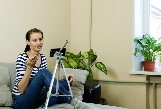 Женщина-блогер разговаривает через приложение для обмена сообщениями во время видеочата на своем мобильном телефоне