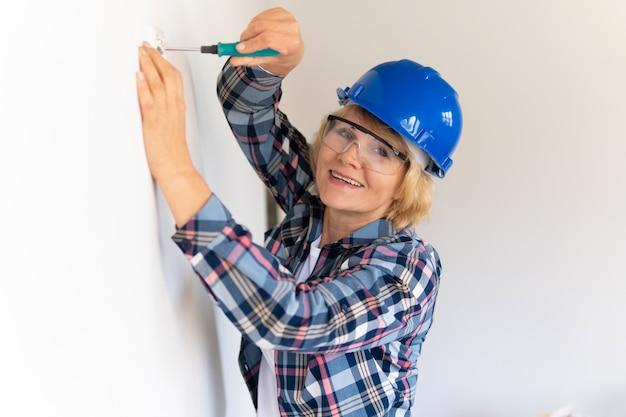 女性のビルダーが新しい建物にコンセントを作ります。中年女性がアパートの修理をします。