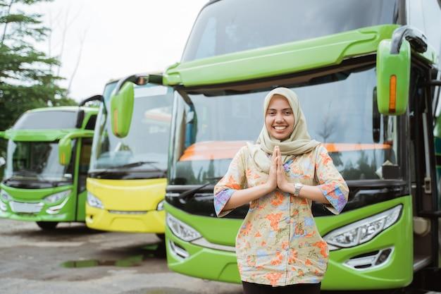 베일을 입은 여성 버스 승무원이 버스를 배경으로 환영의 손짓으로 미소를 짓고 있습니다.