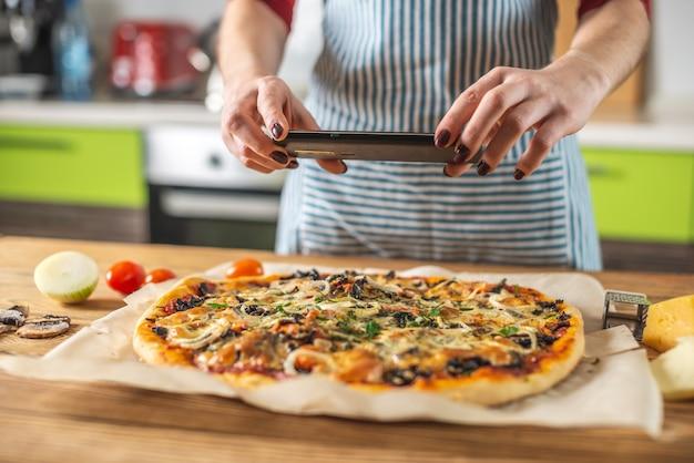 여성 요리사 블로거가 휴대 전화로 집에서 만든 피자 사진을 찍습니다.