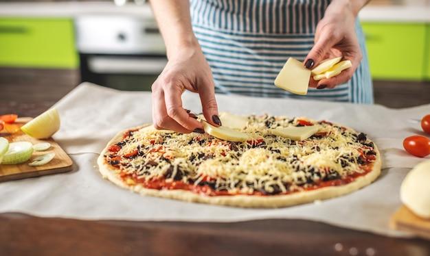 Шеф-повар в фартуке кладет сыр моцарелла на сырую пиццу