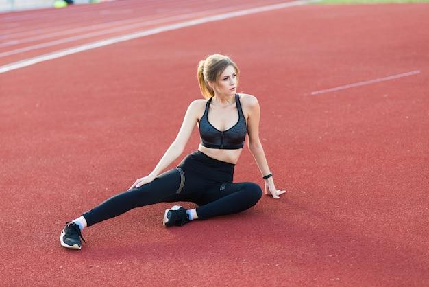 검은 머리를 가진 여성 코치가 스포츠 유니폼을 입은 경기장의 빨간 달리기 트랙에 서 있습니다.