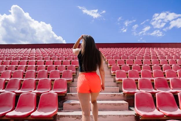 スポーツユニフォームを着た黒髪の女性コーチがスタジアムの赤いランニングトラックに立っています。