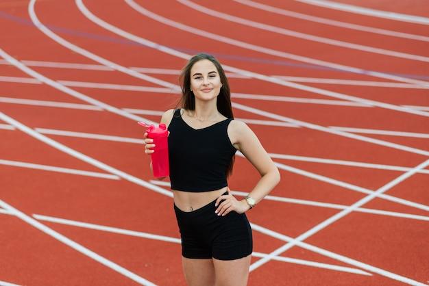 На красной беговой дорожке стадиона стоит темноволосая тренерская женщина в спортивной форме.
