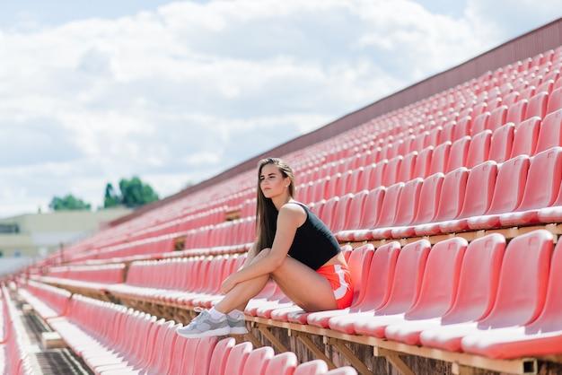 검은 머리카락을 가진 여성 코치가 스포츠 유니폼을 입은 경기장의 빨간 달리기 트랙에 서 있습니다.
