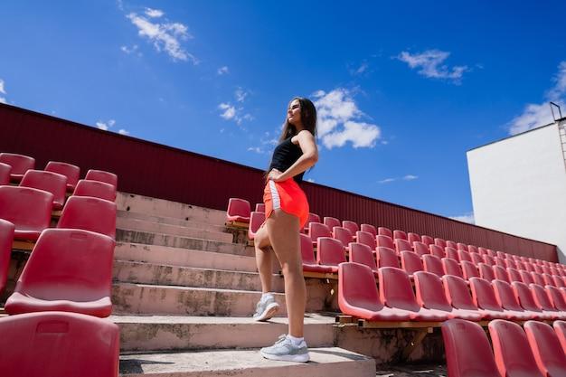スタジアムの赤いランニングトラックに、スポーツユニフォームを着た黒髪の女性コーチが立っています。