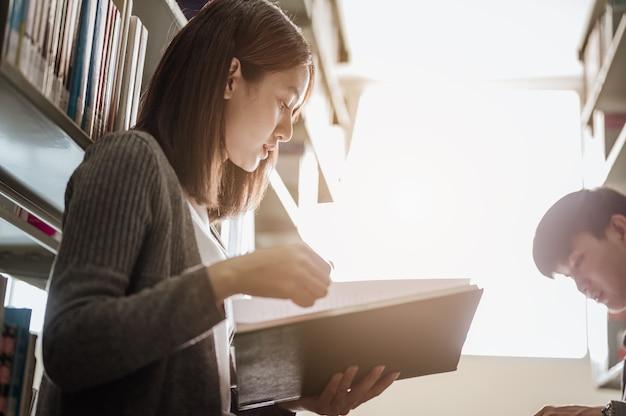 시험을 위해 대학 도서관에 앉아 남자 절친한 친구와 함께 여대생. 교육, 학교, 도서관 및 지식의 개념입니다.