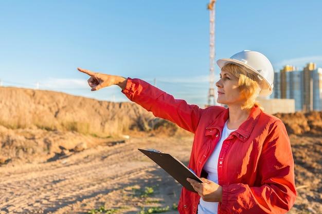 Инженер-строитель на стройке. женщина осматривает.