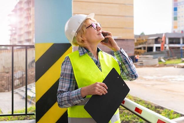 新しい家の背景に緑のベストと白いヘルメットをかぶった女性の建設労働者。彼女は電話で調べて話します。