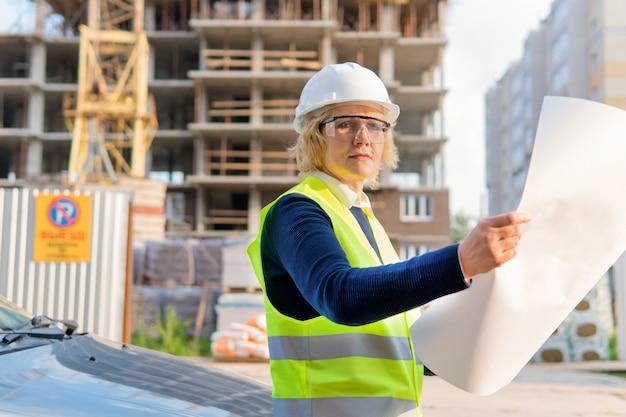 새 건물의 배경에 조끼와 헬멧을 쓴 여성 건설 노동자, 그녀는 집 프로젝트를 살펴 봅니다.