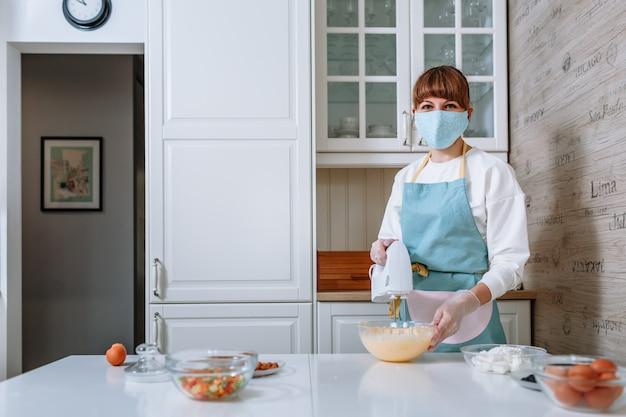 Женщина-повар в медицинской маске и перчатках взбивает тесто для торта