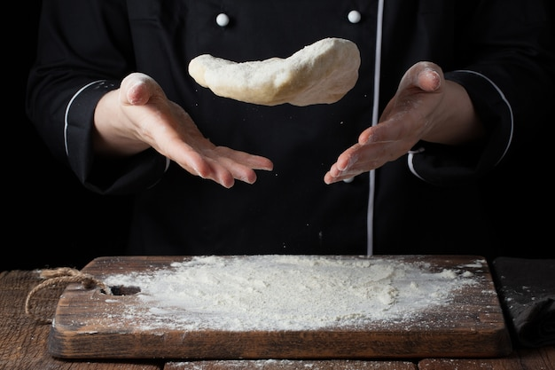 女性料理人がイースト生地を手に投げます。