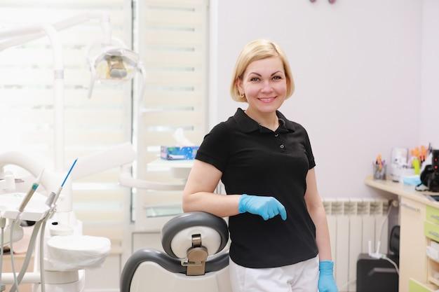 Женщина-дантист в униформе позирует на фоне стоматологического оборудования в стоматологическом кабинете.