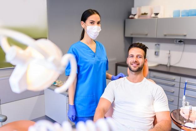 Женский стоматолог лечит пациента в стоматологической практике