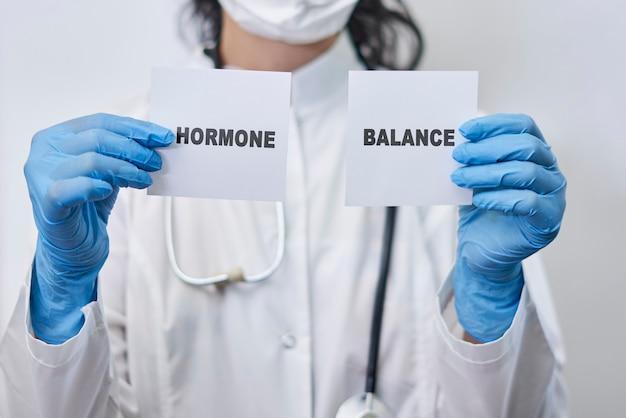 호르몬 균형 단어 호르몬 균형 개념이 있는 두 개의 흰색 카드를 들고 있는 여성 의사