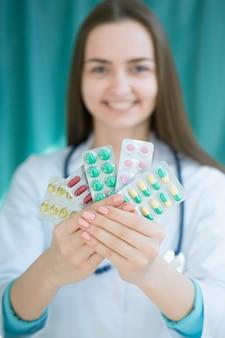 Женщина-врач держит тарелку с таблетками в руках. с глубиной резкости изображения.