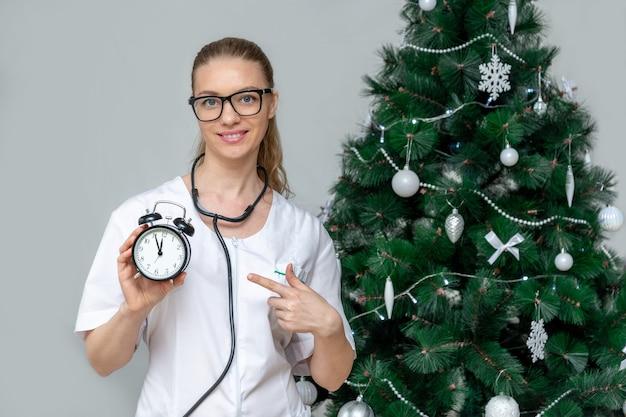 Женщина-врач держит будильник возле елки.
