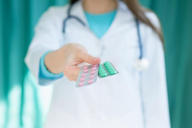 Женщина-врач протягивает пациенту руку с таблетками, фото с глубиной резкости