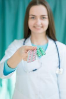 Женщина-врач протягивает пациенту руку с таблетками