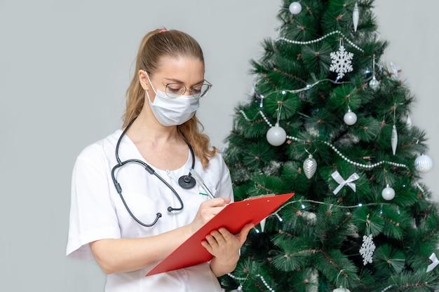 サージカルマスクを着用した女性医師が、クリスマスツリーの近くにクリップボードを持っています。
