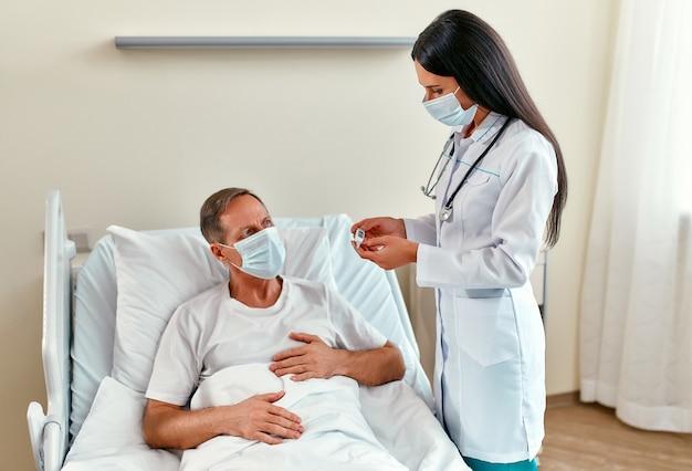 보호용 의료 마스크를 착용 한 여성 의사는 코로나 바이러스 또는 코로나 19 전염병 기간 동안 현대 병원 병동에서 재활을 받고있는 성숙한 남성 환자의 체온을 측정합니다.