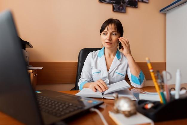 Женщина-врач в белом халате сидит за своим столом в офисе, смотрит в ноутбук и разговаривает по телефону. врач работает. медицинское обслуживание и медперсонал.