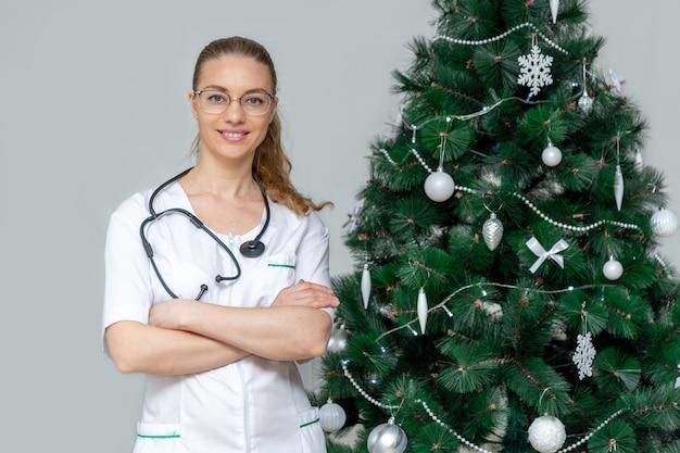 白い制服を着た女医がクリスマスツリーの横で微笑む。