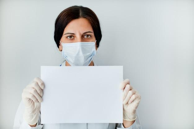 제복을 입은 여성 의사 비문에 대 한 장소를 가진 하얀 시트를 보유하고있다.