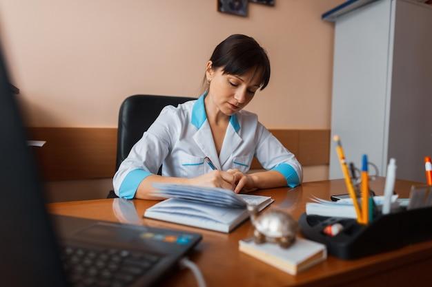 Женщина-врач в белой медицинской форме сидит за деревянным столом в офисе и составляет график работы персонала. рабочие дни. врач работает