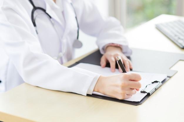 女性医師が病院の診察室で患者の状態に関するレポートを書いています。