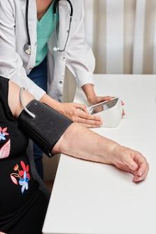 여성 의사가 환자의 혈압을 측정합니다.