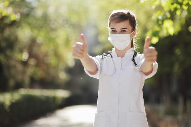 防護マスクをした女性医師または看護師が手でクラスを見せている