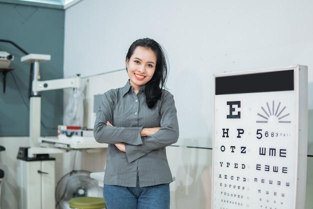 眼科クリニックの診察室にある視力検査キットの横でポーズをとる女性医師
