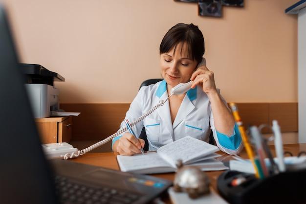 Женщина-врач сидит за своим столом в офисе в больнице, разговаривает по телефону и делает записи в блокноте. современная медицина.