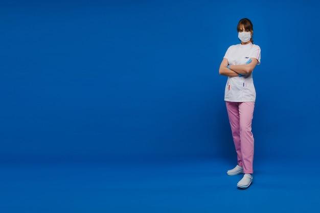 女医師は、青い背景で隔離の医療マスクに立っています。青い背景の白い服を着た看護師