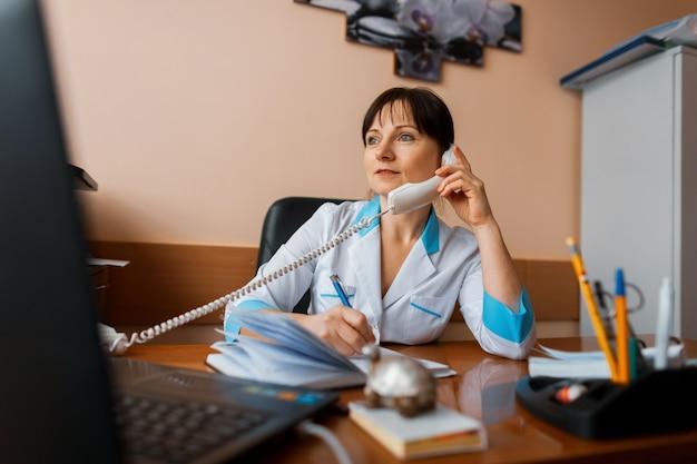 Женщина-врач разговаривает по телефону с одним из пациентов и делает записи в блокноте. врач работает. понятие о медицине.