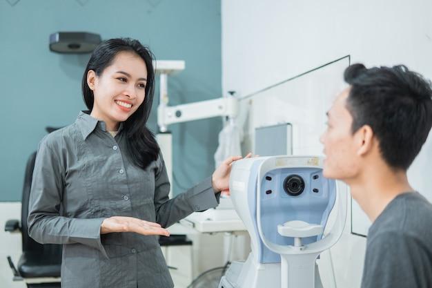 眼科クリニックの診察室で男性患者と一緒に装置を使用している女性医師