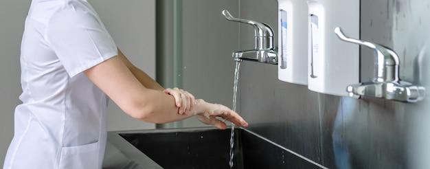 女医がステンレス製の流しの流水で石鹸で手をよく洗う