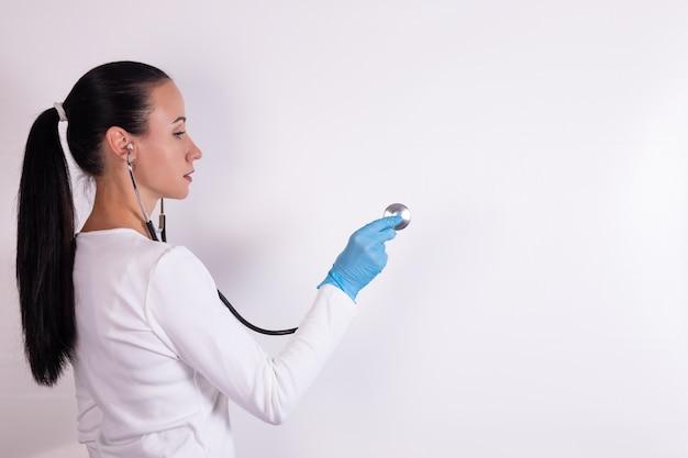 Женщина-врач со стетоскопом, слушая, изолированные на белом фоне