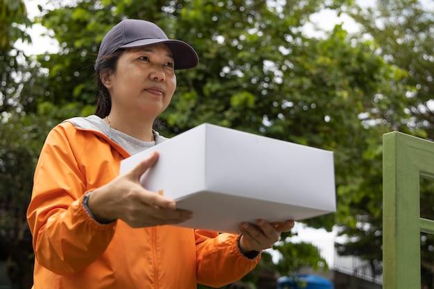 オレンジ色のローブを着た女性従業員が、白い箱に入った贈り物を家の前に届けました。